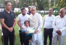 Advisor Farooq Khan presenting a memento to young athlete in Srinagar.