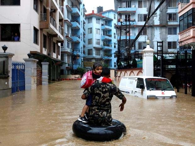A member of Nepalese army carrying a child walks along the flooded colony in Kathmandu, Nepal
