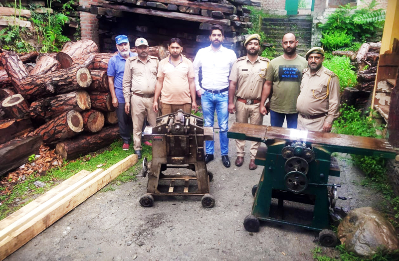 Forest Department officials showing seized illegal planer machines at Bhaderwah on Monday. -Excelsior/Tilak Raj