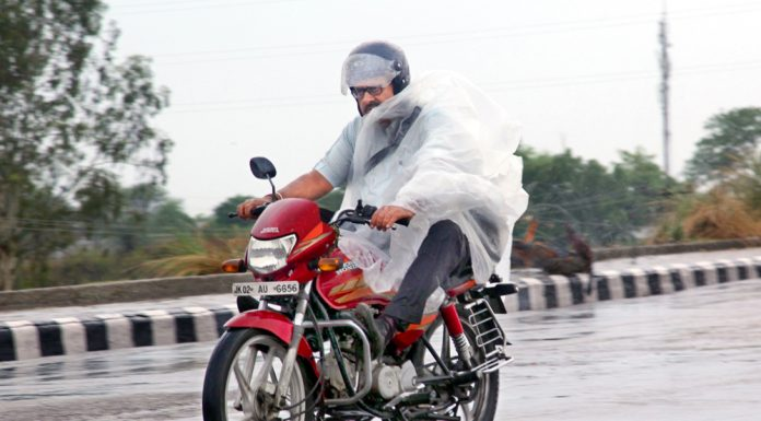 A bike rider covers himself while driving during rains in Jammu on Tuesday morning. -Excelsior/Rakesh