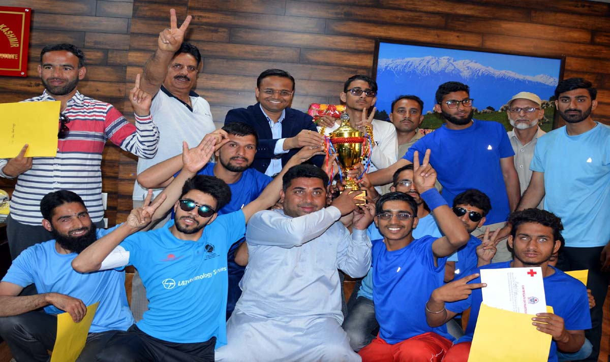 Winners of maiden Cricket tournament for visually impaired posing for a group photograph while holding trophy in Bhaderwah.