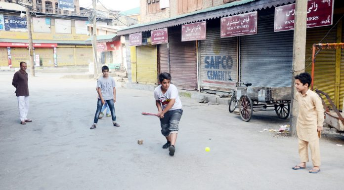 Boys play cricket on a deserted street at downtown Srinagar on Sunday. —Excelsior/Shakeel