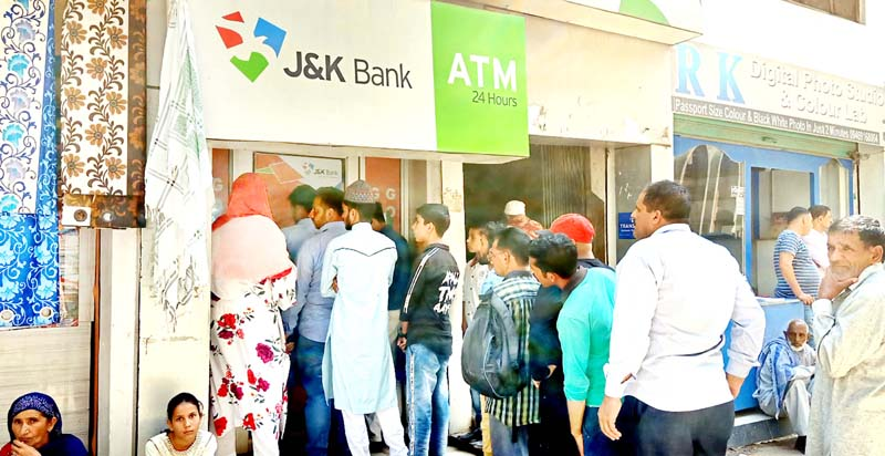 Locals in Mendhar town waiting outside an ATM for withdrawing money.