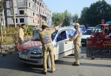 Cops checking vehicles during restrictions in Srinagar on Friday. -Excelsior/Shakeel