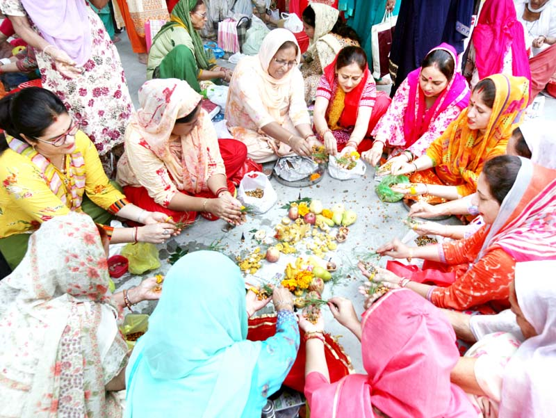 Women performing rituals for long life of their sons on the occasion of 'Bacch Dua' in Jammu on Tuesday. -Excelsior/Rakesh