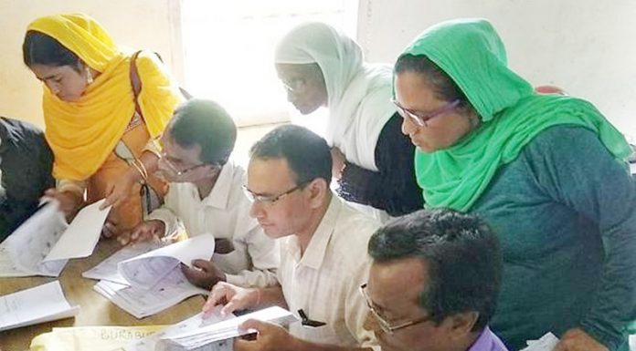 Villagers checking their names in the final list of the NRC in Morigaon district of Assam on Saturday.