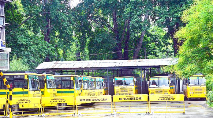 Buses parked in the premises of a school building in Srinagar on Monday. -Excelsior/Shakeel
