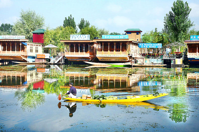 A boatman carries vegetables at Dal lake in Srinagar on Tuesday. -Excelsior/Shakeel