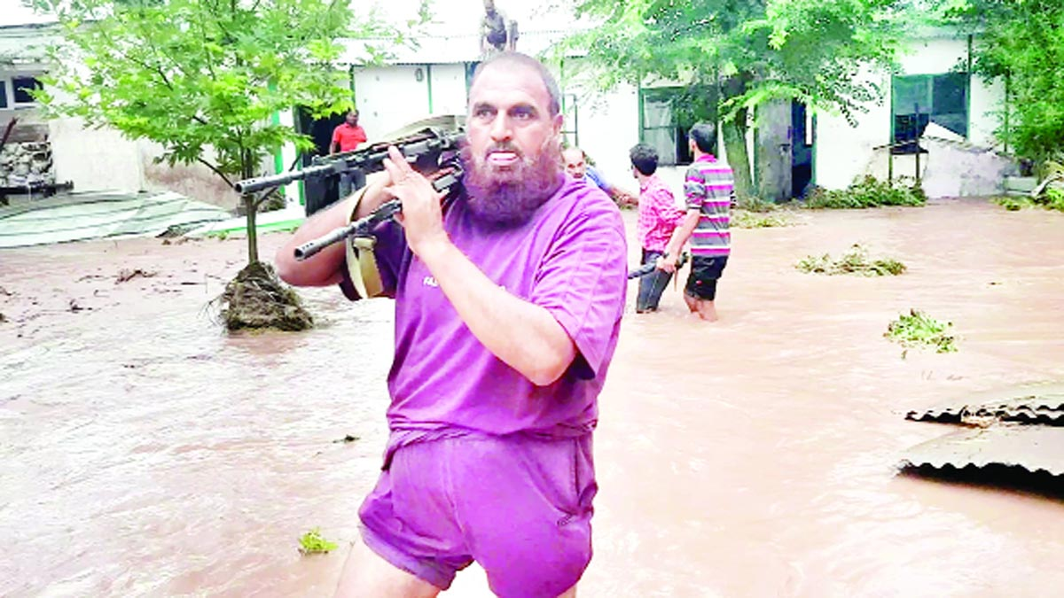 A securityman carrying two guns on shoulder as flood water enters LoC Trade Centre in Poonch. —Excelsior/Ramesh Bali