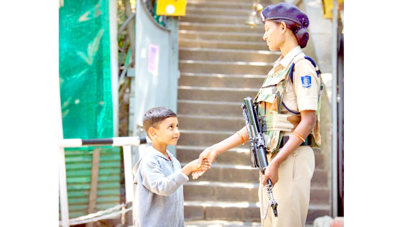 A child shakes hands with woman jawan of CRPF amidst restrictions in Kashmir on Thursday.