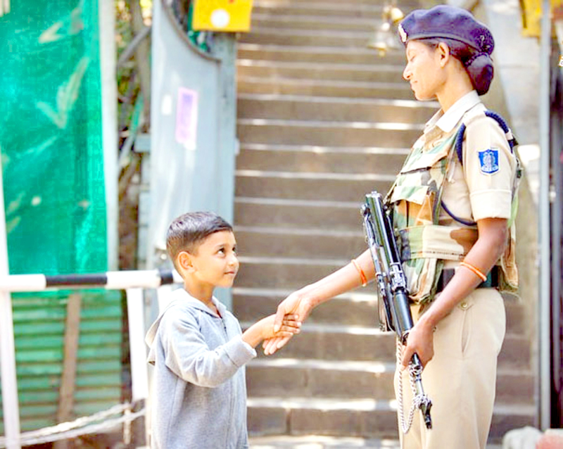 A child shakes hands with woman jawan of CRPF amidst restriction in Kashmir on Thursday.