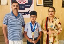 Karateka Vansh Khullar posing along with Management of Doon International School.