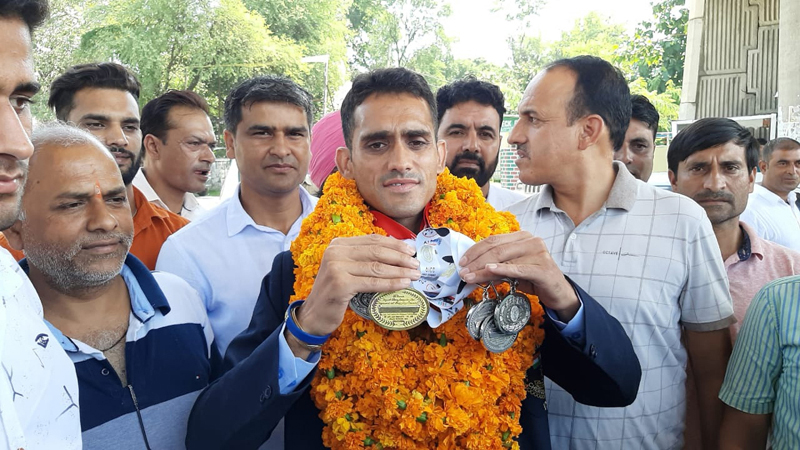 Ace athlete Radhey Kumar being accorded warm reception at Lakhanpur after his return from China.