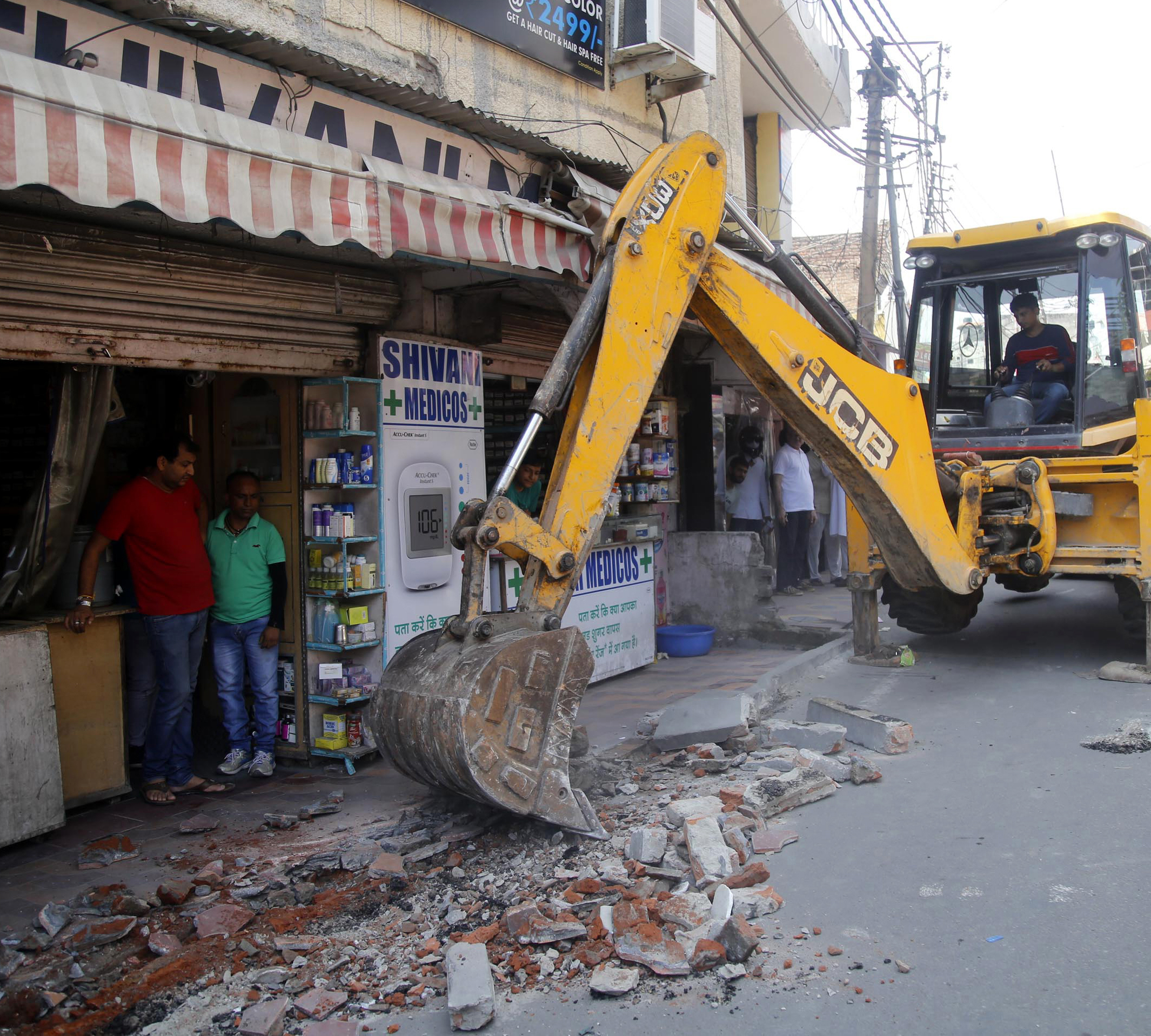 JCB demolishing illegal structure in Sarwal area of Jammu on Thursday. —Excelsior/Rakesh