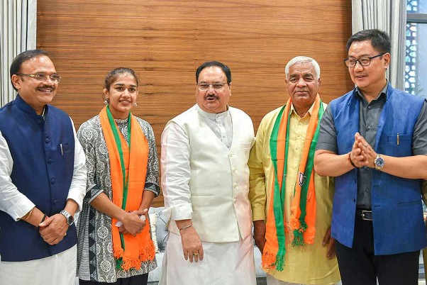 BJP Working President JP Nadda and Union Minister Kiren Rijiju pose for a photograph with the wrestler Babita Phogat and her father Mahavir Singh Phogat after they joined the Bharatiya Janata Party at BJP headquarters, in New Delhi.