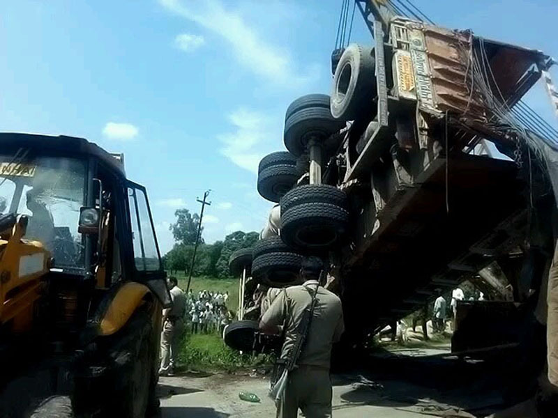 Police inspecting the accident sitewhere a truck overturned on two templos at Roja in Shahjanpur district on Thursday. At least 17 people were reportedly killed in the accident. (UNI)