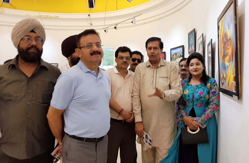 Visitors having a glimpse of art work at National Exhibition of Visual Arts in Amritsar.