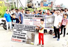 People protesting with banners near Hatli Morh in Kathua. -Excelsior/Pardeep
