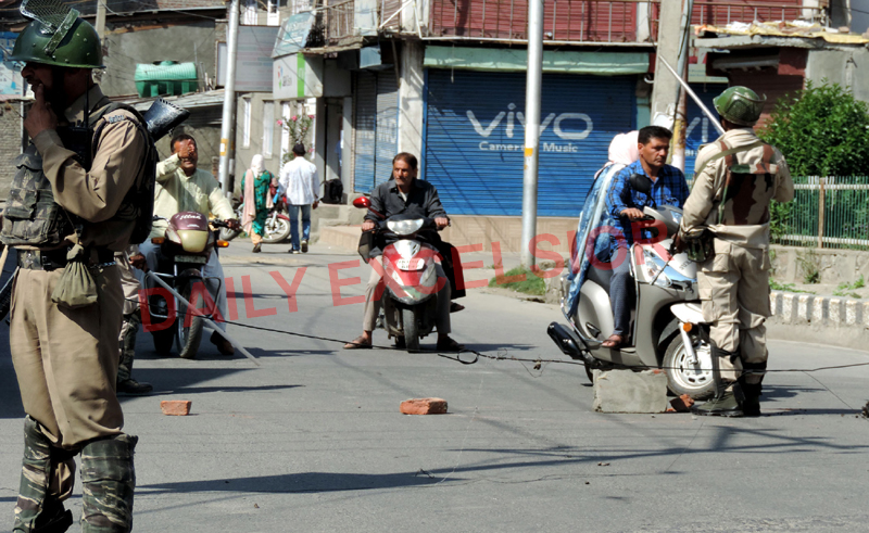 Para-military personnel asking two-wheeler operators to take another route at Hawal, Srinagar on Monday. (UNI)