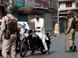 A motor-cyclist pleading before the security forces to allow him to cross the road at Ranger Stop in down town Srinagar on Friday. (UNI)