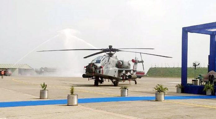 An Apache chopper receives water cannon salute before induction at the Pathankot air base on Tuesday.