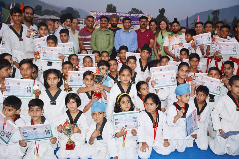 Participants of Tackwondo camp at Poonch displaying medals and certificates while posing for a group photograph with guests during valedictory function.