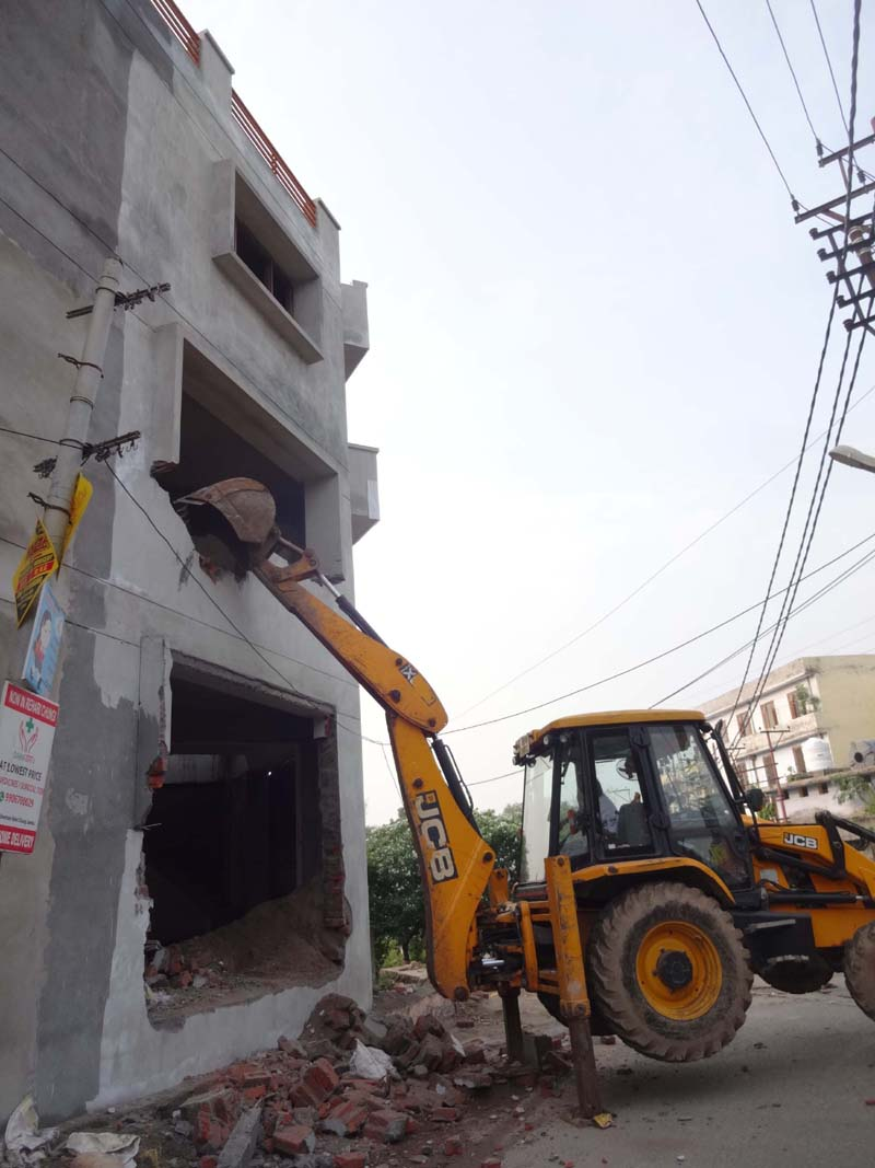 JMC using JCB to demolish a three storey building at Karan Nagar, in Jammu on Friday.