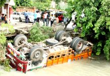 A truck submerged partially in Ranbir canal on Jammu-Akhnoor Road. -Excelsior/ Rakesh