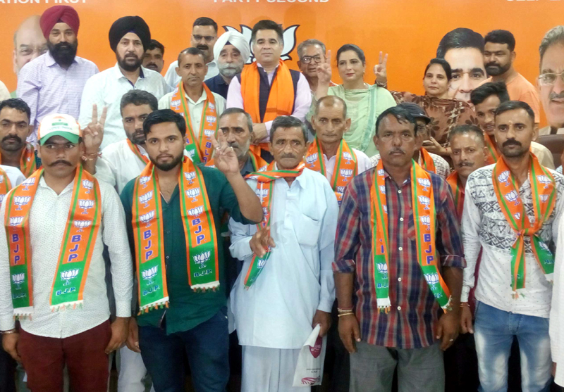 BJP leaders posing for a photograph with new entrants in the party at Jammu on Monday.