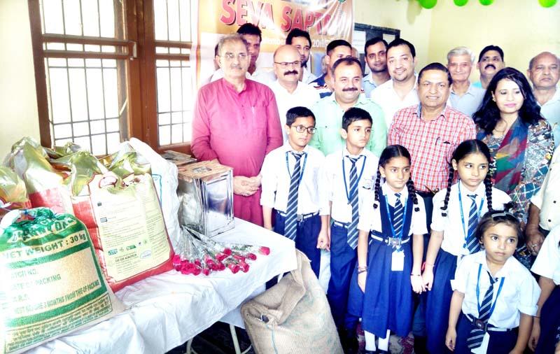 Former Deputy CM, Kavinder Gupta & MLC, Vikram Randhawa distributing food items to the SOS Home Children at Jammu on Friday.