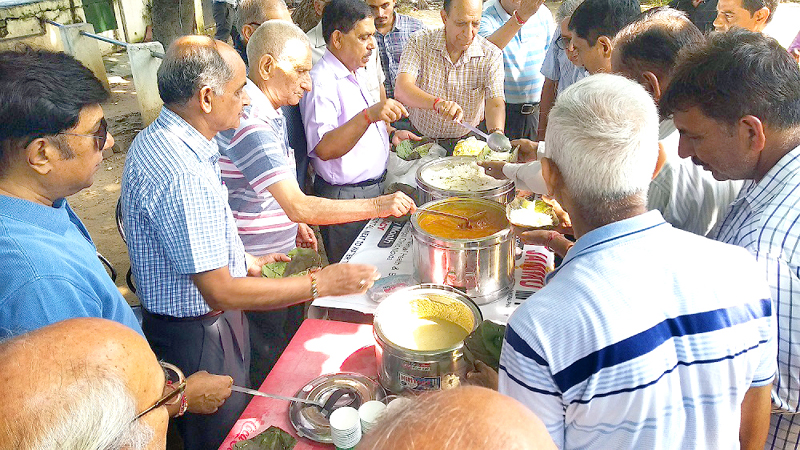 Members of Senior Citizen's Rejuvenation Centre distributing food items during 'langar' at Government Hospital Gandhi Nagar on Monday.