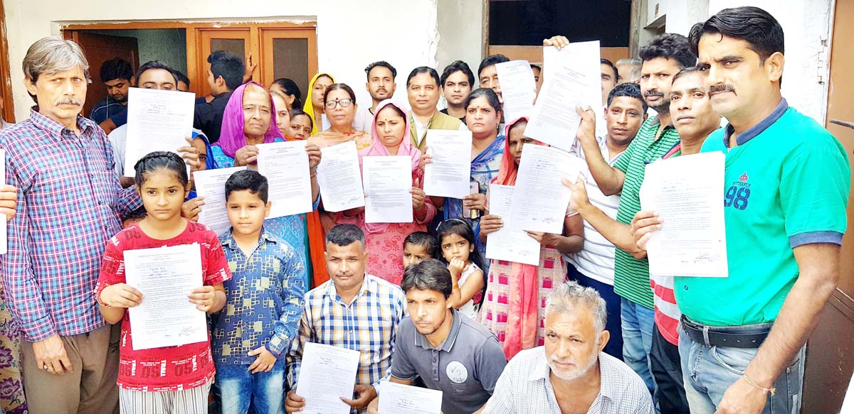 Former minister, Sat Sharma posing with people after distributing PMAY approval letters.