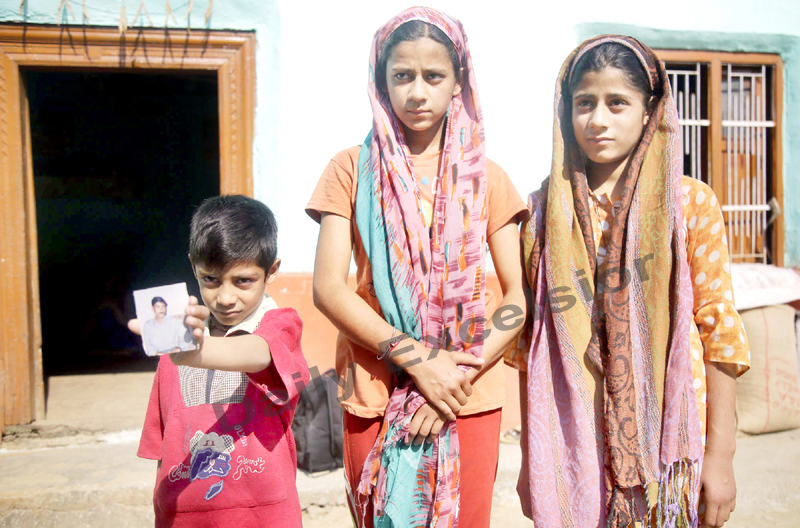 Children of slain truck driver displaying a photograph of their father. -Excelsior/Rakesh