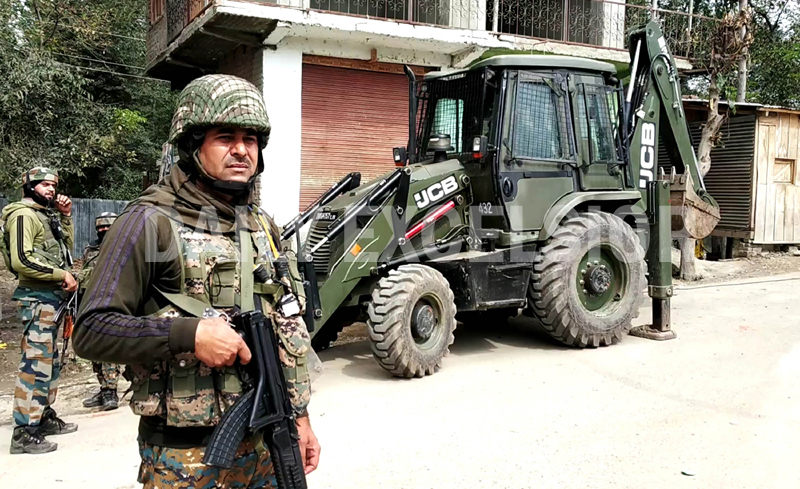 Security personnel standing guard near the encounter site at Awantipora on Tuesday. (UNI)