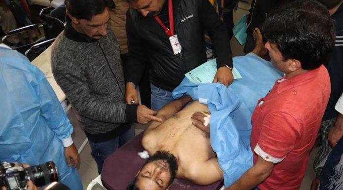 A civilian injured in grenade attack being taken to hospital in Srinagar on Saturday. -Excelsior/Shakeel