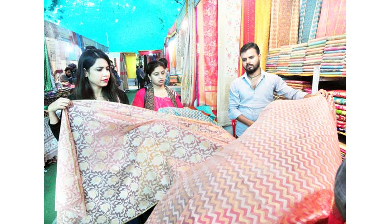 A salesman displaying Silk Sarees at Silk Expo in Jammu on Sunday. -Excelsior/Rakesh