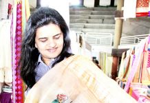 A customer having glimpse of a saree during Silk India Exhibition at Kala Kendra, Jammu on Thursday.