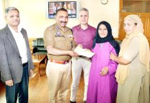 DGP Dilbag Singh presenting cheque to mother of a martyr at Srinagar on Tuesday.
