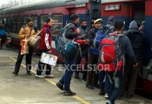 Commuters boarding train at Srinagar railway station on Sunday. -Excelsior/Shakeel