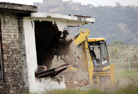 A Forest JCB demolishing concrete illegal structure raised by land grabbers at Dwara in Sidhra area of Jammu on Saturday. —Excelsior/Rakesh