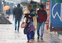 Woman takes umbrella cover during rain in Srinagar on Friday. -Excelsior/ Shakeel