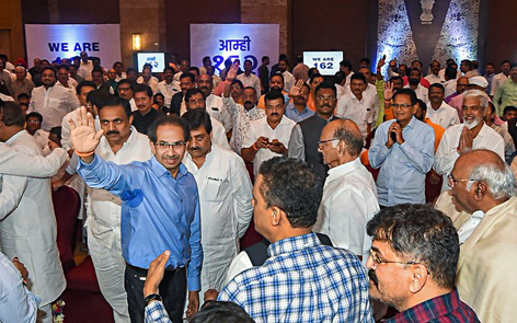 Shiv Sena leader Uddhav Thackeray waves as Sena-NCP-Cong MLAs hold show of strength in Mumbai on Monday.