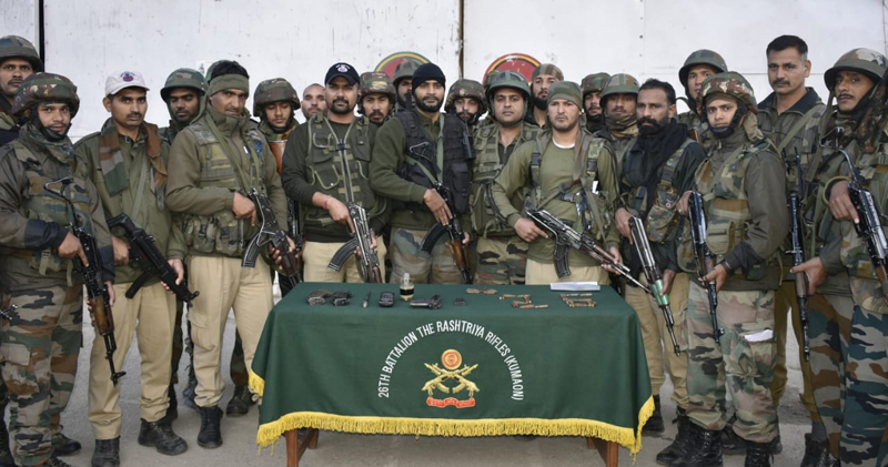 Security personnel pose with recoveries made from an OGW in Sangram Bhata, Kishtwar on Monday.