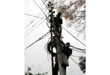 Employees of Power Development Department rectify the fault on top of an electric pole in Srinagar. (UNI)