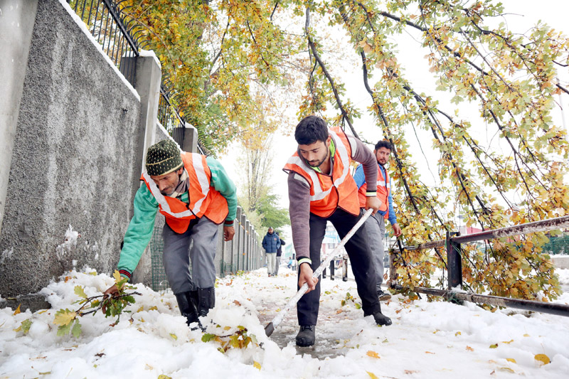 SMC casual labourers clearing snow from footpaths in Srinagar. -Excelsior/Shakeel
