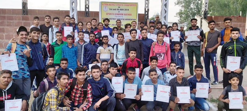 Top three position holders of Kathua District Athletics Championship and dignitaries posing for group photograph at sports stadium, Kathua on Monday.