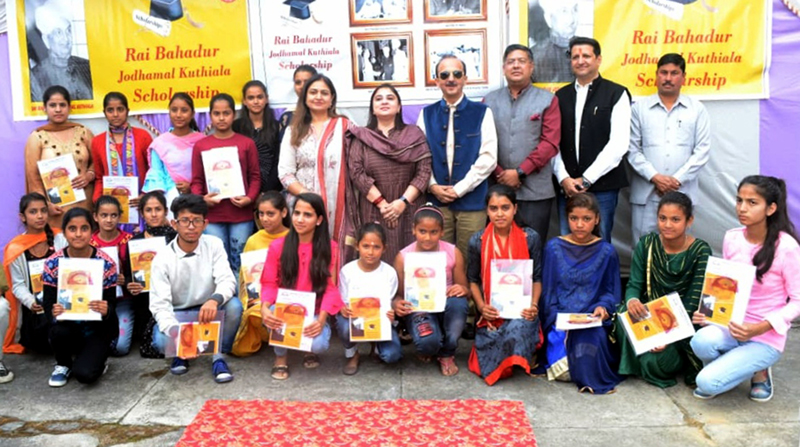 Students posing for photograph with dignitaries after being awarded scholarships.