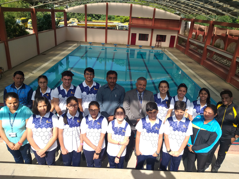 Selected swimmers of Jodhamal Public School posing for photograph with their Principal Dr Deep Khare.