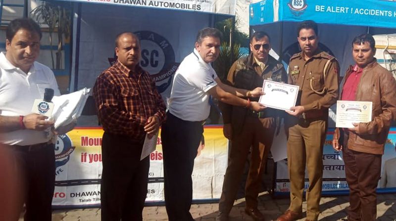 Ravinder Bhat (founder of Road Safety Champions) presenting appreciation certificate to a police officer during an awareness camp on road safety at Bantalab, Jammu.