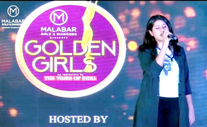 Akshita displaying singing skills during 'Golden Girls Hunt' event at Jain University in Bengaluru.